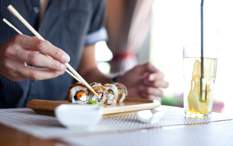 Close up of a person using chopsticks to eat sushi