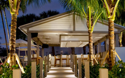 An outdoor walkway lit up at night leading to a covered seating area and lined with palm trees and greenery