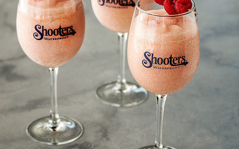 Three glasses of rose slushee drinks in wine glasses with the shooters logo and each garnished with three raspberries