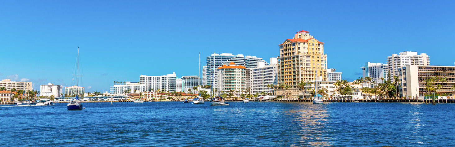 A view of downtown buildings from the ocean water with several sailboats in the water
