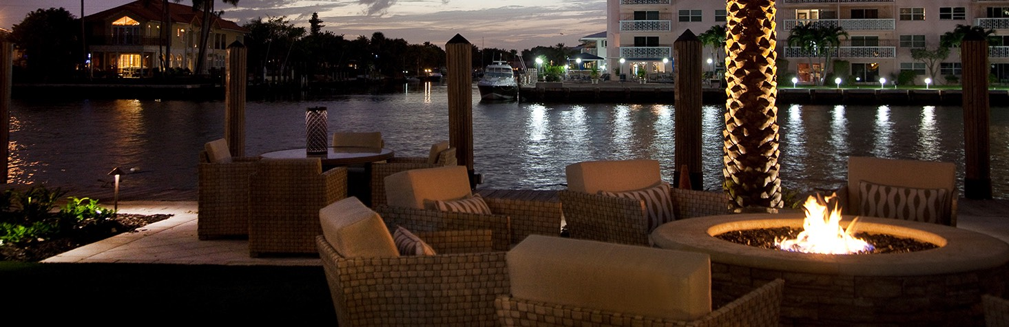 An outdoor fireplace area surrounded by cushioned chairs by the intercostal waterway