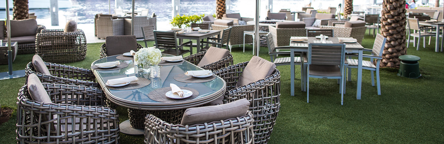 A rounded rectangular six person outdoor dining table on grass surrounded by additional tables, chairs, and couches