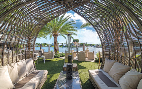 wicker birdcage structure overtop couches on the grass patio with a view of the water