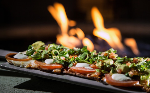 flatbread pizza with tomatoes, mozzarella and greens in front of a fire