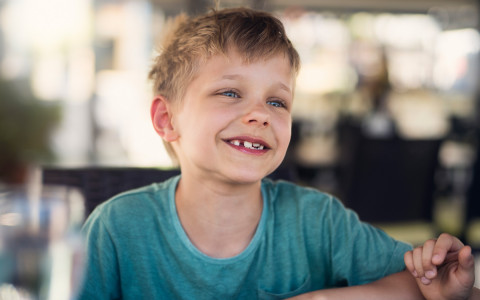 A small boy sitting at the table eating spaghetti smiling