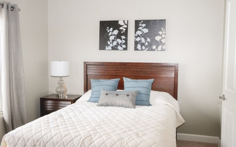 a bedroom with white linens and a wood bed