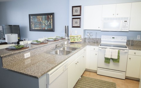 a white kitchen with granite countertops