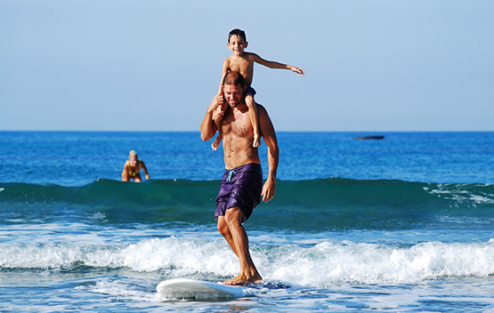 Man surfing with child on sholders