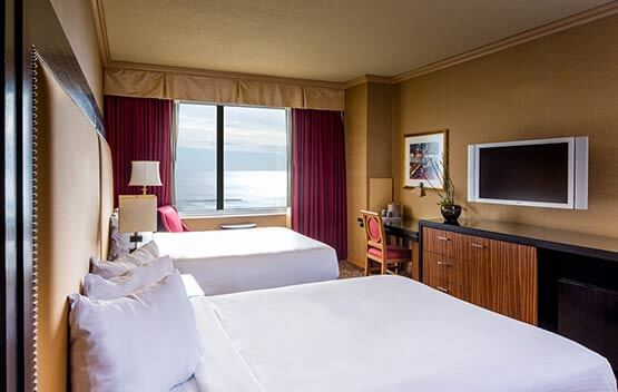 double room with 2 queen beds. Across from a desk, dresser, mounted tV and an ocean view from the side window.