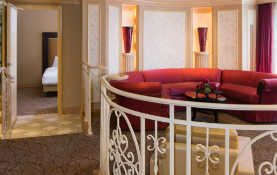 super suite has raised living area with extravagant red furniture and master room adjacent