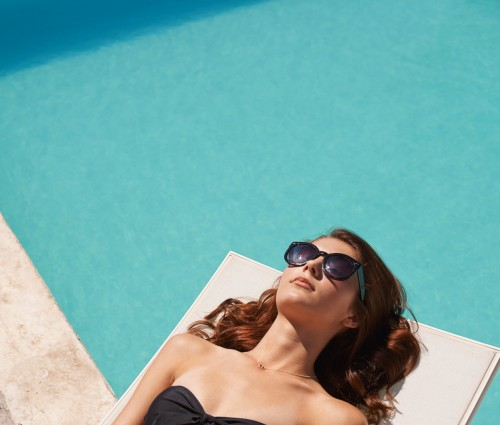 woman tanning by the pool
