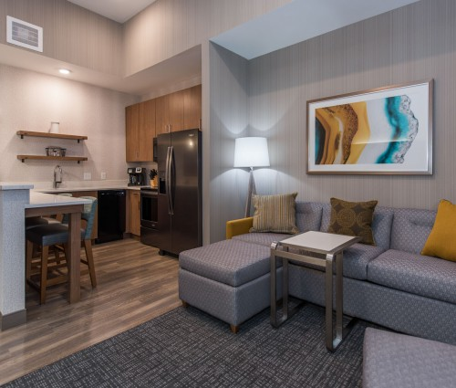 The living room has a couch and opens up next to the kitchen that features a refrigerator, barstool seating, sink, and additional kitchen appliances.