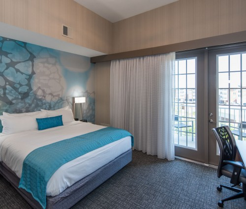 One bed with white linens and turquoise blue pillow and sham. The wallpaper behind the bed has a design with white, blue, yellow and grey colors in it. There are windowed doors that lead to the balcony. The doors have a white curtain. On the other side of