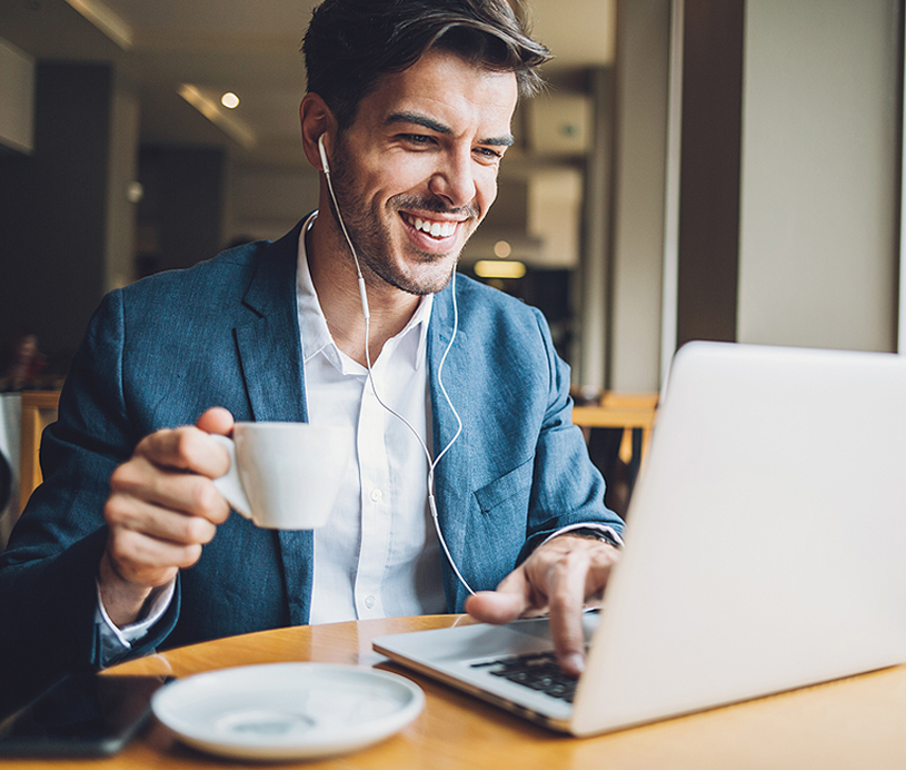 man drinking coffee and looking at a computer
