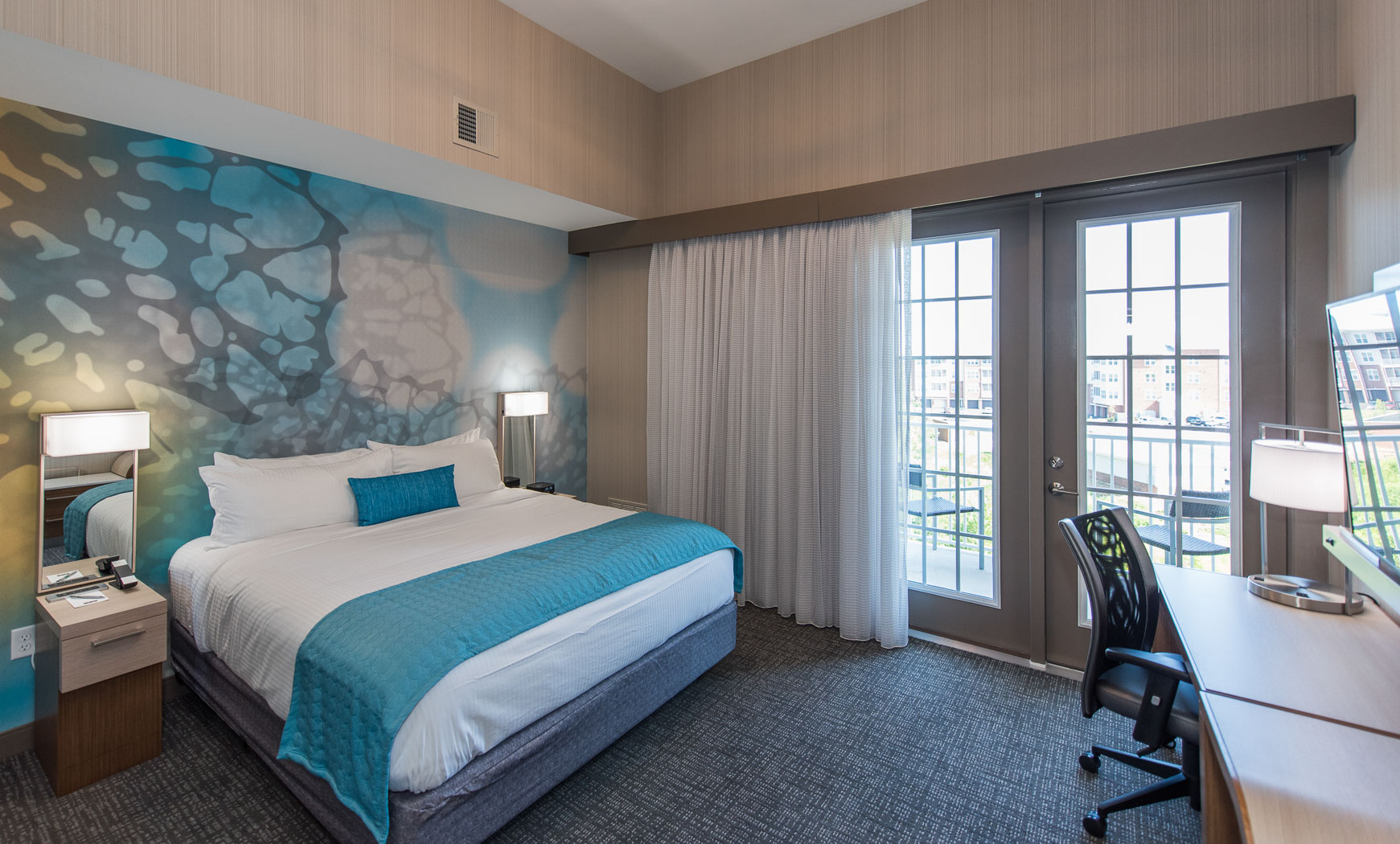 2 Double Beds with white linens and turquoise blue pillow and sham. The wall behind the bed have a wallpaper that include white, blue, yellow and grey's in the design. There is also a closet with a mirror door and shelving inside.