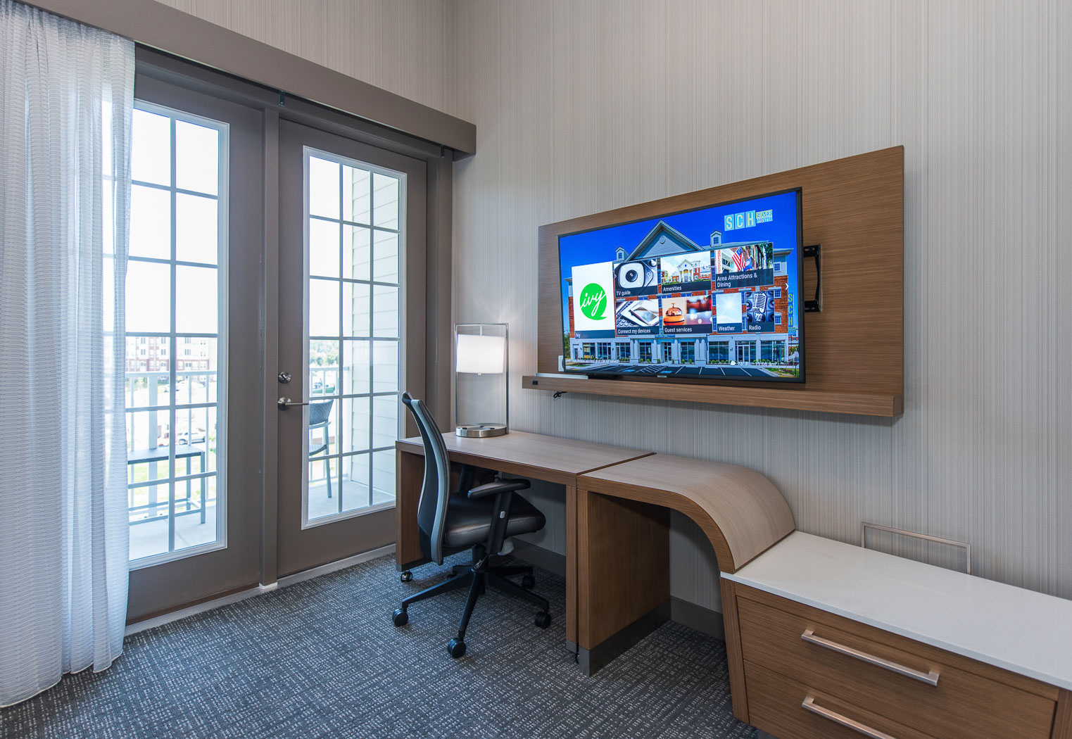 TV mounted on the wall with a small desk and chair underneath along with some drawers. The TV and desk are near the balcony door.