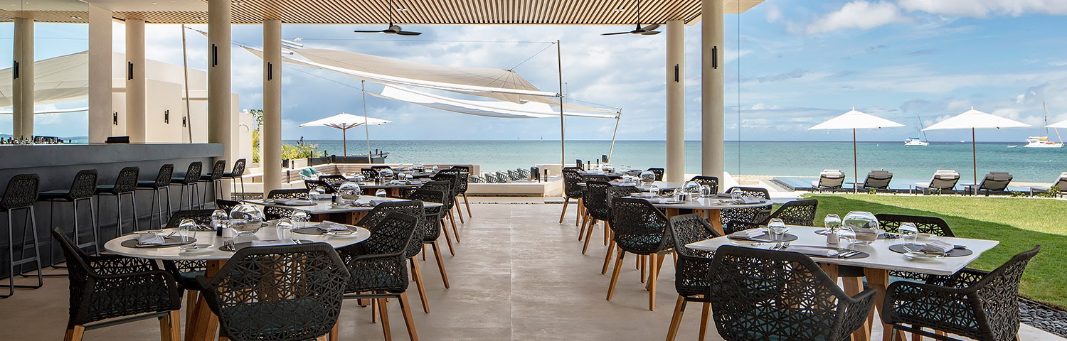 Covered outdoor oceanfront dining area featuring black chairs, white tables, and barstools at the bar
