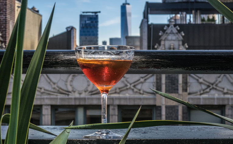 glass with liquor on rooftop ledge
