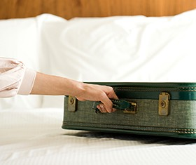 woman holding a briefcase on top of a bed