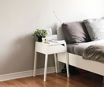 bedroom with grey sheets and a white nightstand