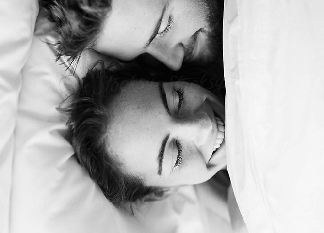 couple smiling and laying in bed