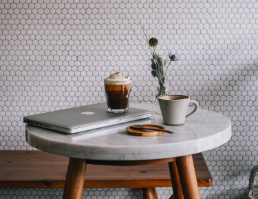 a laptop, plant and coffee cups sit on a small marble side table with wooden pegs