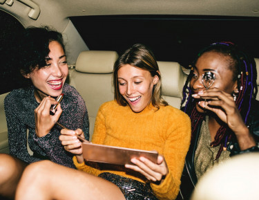 three women sitting in the back of a car doing their makeup and laughing
