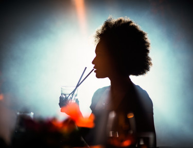 a woman sipping on a drink with a bright light behind her