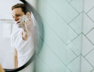 a man looking into a mirror grooming his beard