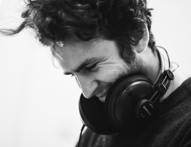 black and white image of a man wearing headphones looking down and smiling