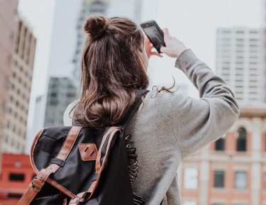 a woman wearing a black backpack taking a picture on her phone of a city building