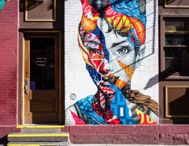 a colorful mural of a woman on a brick building