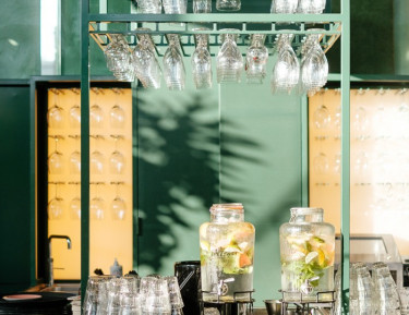 bar area with green accent colors, glassware hanging from a rack, and two pitchers of fruit infused water