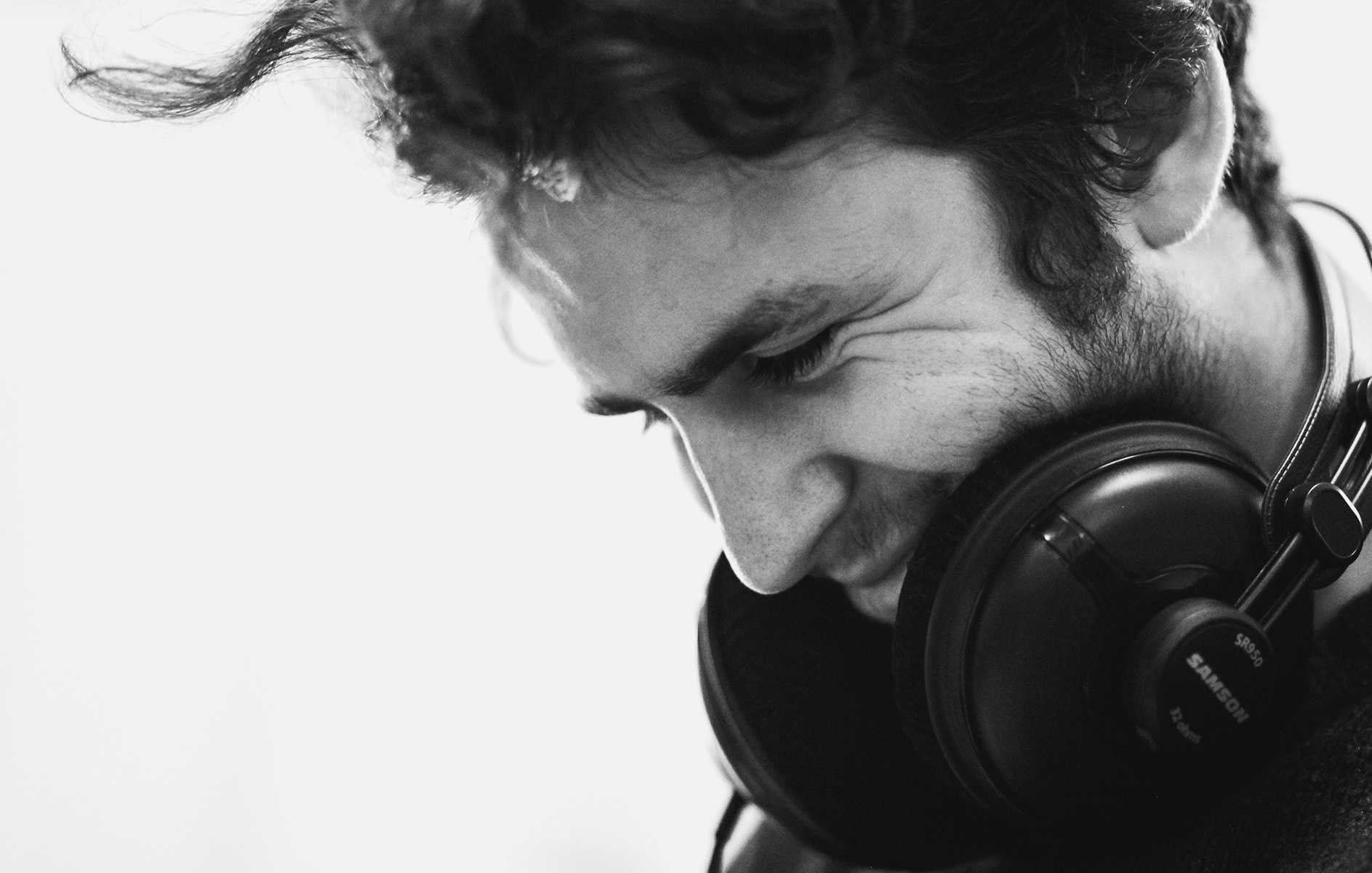 black and white image of a man wearing headphones around his neck looking down