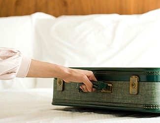 a woman putting a green suitcase on top of a white linen bed
