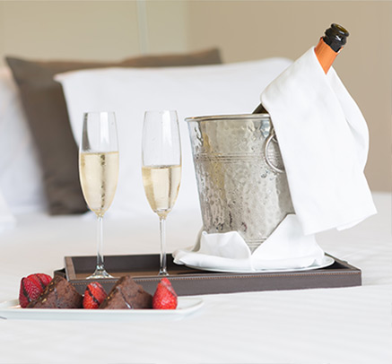 Champagne and chocolate covered strawberries on a plate, on a bed