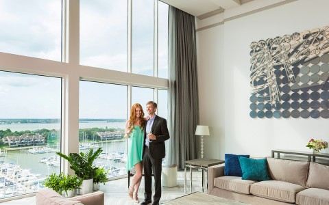 Couple enjoying drinks in a living room with a view of the water