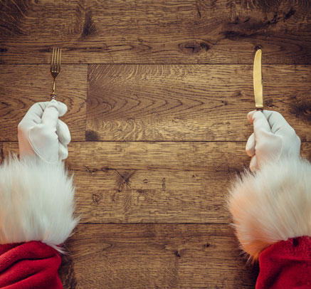 Santa Clause's hands holding a fork and knife