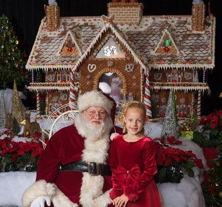 Young girl with Santa taking holiday photo in front of South Shore's Gingerbread House