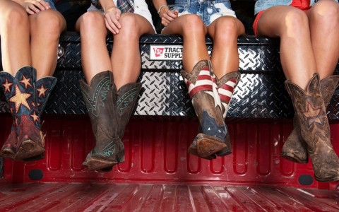 women wearing cowboy boots sitting on a truck bed