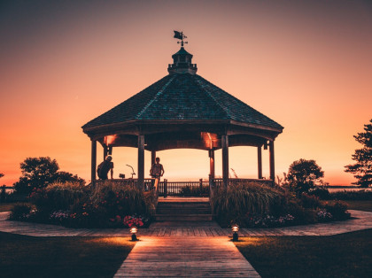 gazebo with people on bikes during the sunset