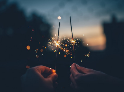 hands holding sparklers during dusk outside