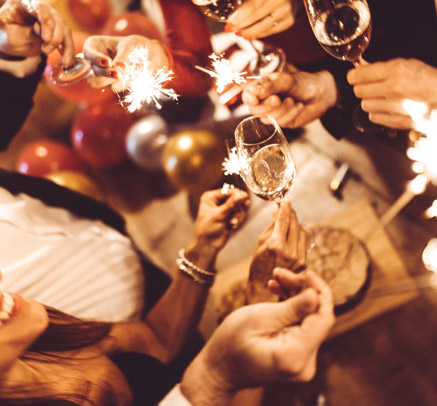 a group of friends celebrating new years eve with champagne and sparklers