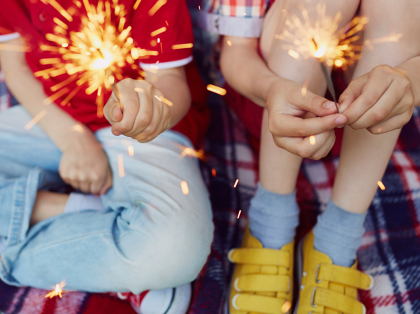 a boy and a girl holding sparklers