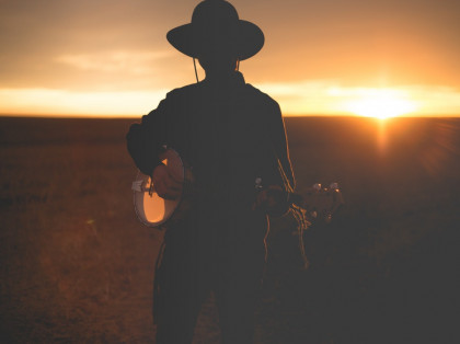man playing banjo during the sunset outside