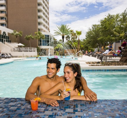 a man and a woman enjoying drinks in a pool