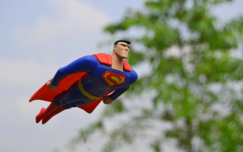 superman action figure flying in the sky