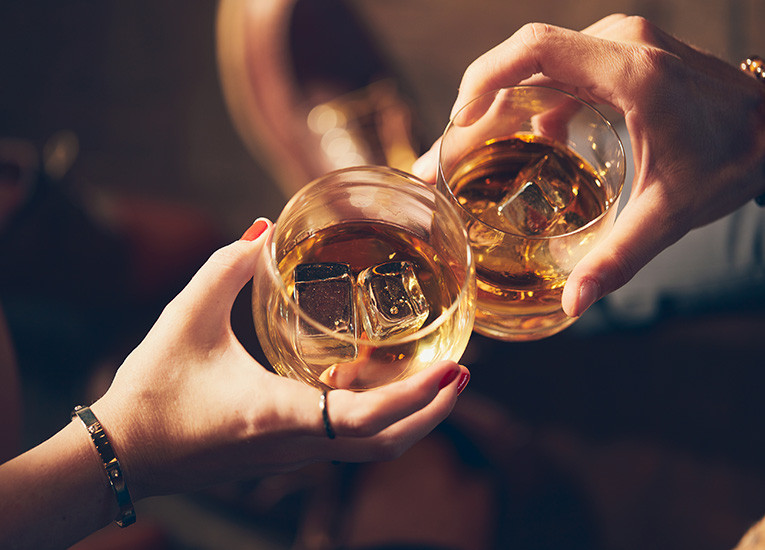 Close up of two people toasting with bourbon