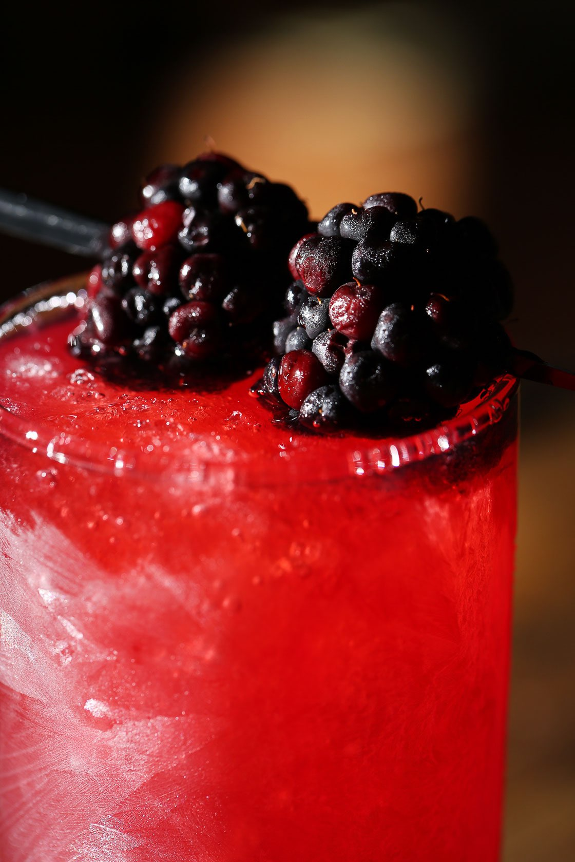 Close up of red drink with blackberries on the top