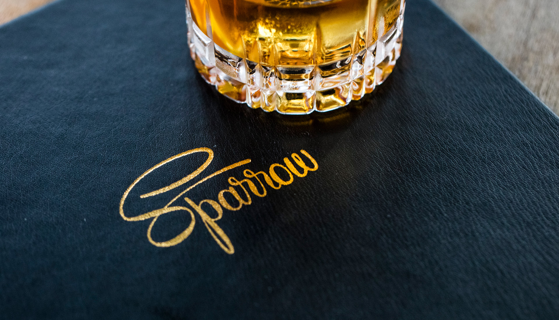 glass of whiskey on top of a sparrow menu book